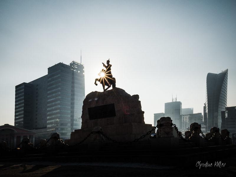 La place Gengis Khan. Au 1er plan, la statue du héros de l'indépendance mongole Damdin Sukhbaatar. A droite, la tour Blue sky, le plus haut building d'Oulan Bator (105 mètres)